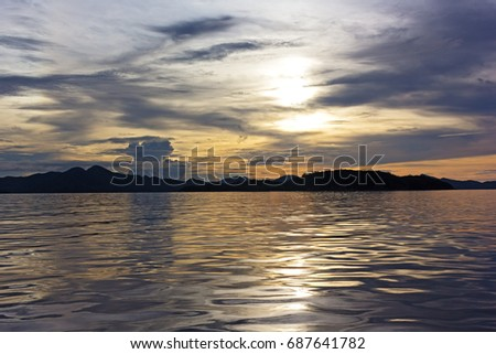Sunset over the mountains on the horizon on Coron Island, Philippines. Quiet sea at sunset with mountain ridges. #687641782