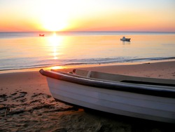 Sunset over the quiet, sheltered water of Maputo Bay, Mozambique, as seen from KaNyaka Island, with part of a small rowing boat in the foreground