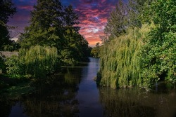 Sunset over the river Avon running through Chippenham Wiltshire. Weeping willow drooping into the water. Other broad leaf trees on grassy banks.