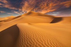 Sunset over the sand dunes in the desert. Aerial view