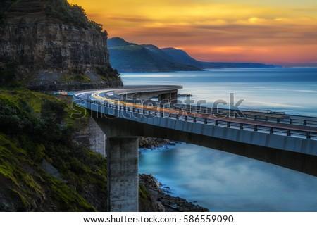 Sunset over the Sea cliff bridge along Australian Pacific ocean coast with lights of passing cars near Sydney, Australia. Long exposure.