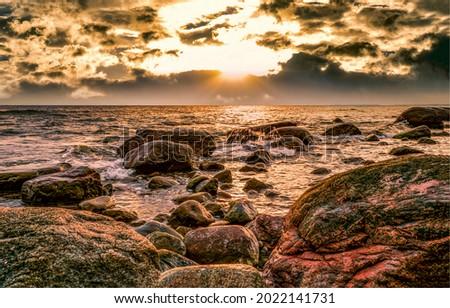Sunset over the sea horizon. Sea rocks at sunset. Sunset over sea. Sea sunset view