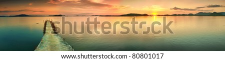 Sunset over the sea. Pier on the foreground. Panorama
