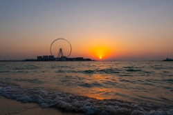 Sunset over the sea view to the Dubai Eye giant Ferris at artificial island Bluewaters Island  close to JBR beach. Amazing sunset on the beach in UAE.