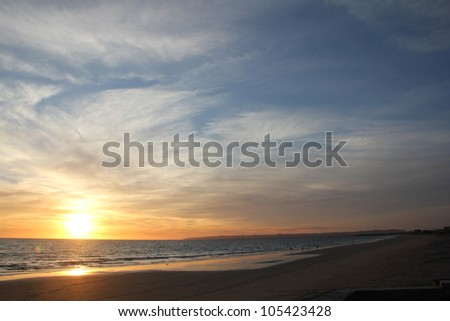 Sunset over the sea with a blue sky - stock photo
