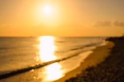 Sunset over the seashore. Background on the theme of the sea and nature. Image is out of focus