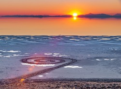 Sunset over the Spiral Jetty, a giant earthwork sculpture by Robert Smithson in the Great Salt Lake of northern Utah, United States.