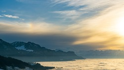 sunset over the valley of Rhein with fog in the deep and snow on the mountains. Clouds of veil come from the mountains and create an impressive atmosphere with a halo. the alps of Vorarlberg.