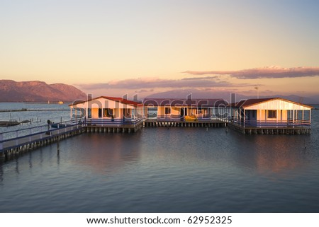 sunset over the water houses