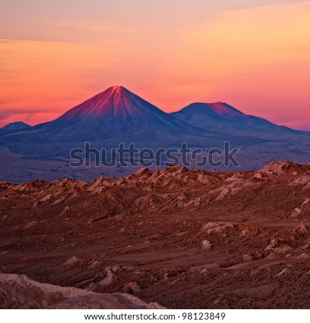 sunset over volcanoes Licancabur and Juriques, Chile - stock photo