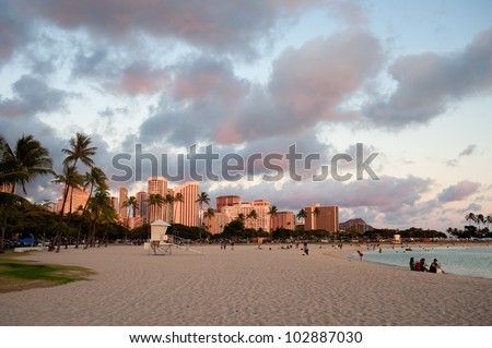 Sunset over Waikiki beach with modern buildings in the back