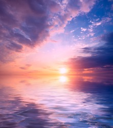 Sunset painted the sky in pink and purple over the sea. Natural dawn composition