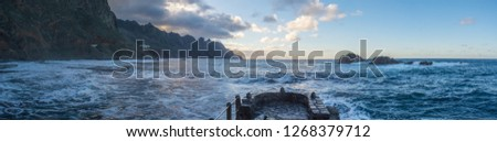 Sunset Panorama of beach Playa Roque des Las Bodegas with wild anaga mountains near Santa Cruz de Tenerife - looking west on Atlantic Ocean in stormy weather in january #1268379712