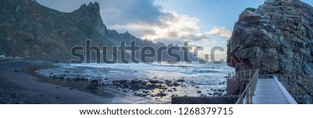 Sunset Panorama of beach Playa Roque des Las Bodegas with wild anaga mountains near Santa Cruz de Tenerife - looking west on Atlantic Ocean in stormy weather in january #1268379715