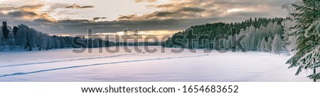 Sunset panorama over winter forest at sides and frozen river in the middle. Typical Northern Sweden landscape - birch and spruce tree covered by hoarfrost - very cold day, Lappland, Sweden Stock foto ©