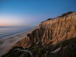 Sunset panorama view of Arriba Fossil da Praia da Gale Fontainhas beach hoodoo fairy chimney earth pyramid rock formations canyon erosion, atlantic ocean Melides Portugal Europe