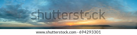 Sunset panorama with beautiful contrast between blue sky and warm yellow light #694293301