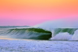 Sunset Perfection, an image of a wave breaking during sunset in Japan the wave is a perfect right hand barrel wave and the sunset is after a typhoon with stunning pinks and purples and hints of orange