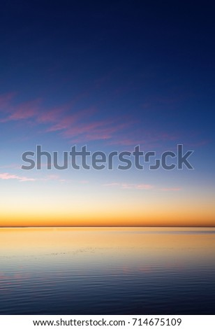 Sunset. Quiet landscape with relaxing atmosphere, sunset when water meets the sky in orange #714675109