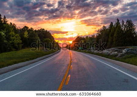 Sunset Rays Poking Through Trees on Open Country Road in  Ontario Canada
