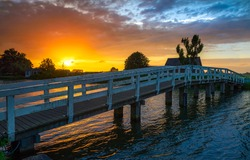 Sunset river bridge in rural scene. Wooden bridge river sunset. Sunset river bridge view. Sunset rural river bridge