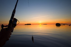 Sunset river perch fishing with boat and rod, hauntingly beautiful night, fish rising, evening bite, successful fishing and good trophy. Men's entertainment