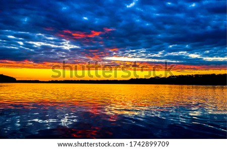 Sunset river water cloudy sky view. River sunset horizon view. Sunset river sky clouds landscape