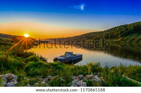 Sunset rural river boat view. Sunset river boat scene. Sunset river boat. River boat sunset scene