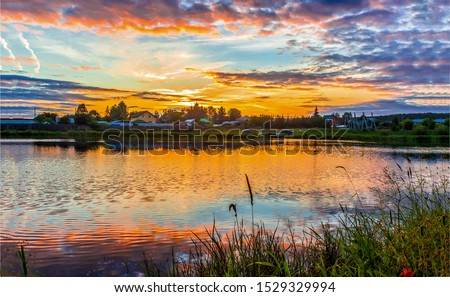 Sunset rural river landscape. Village river sunset landscape. Sunset river village view. Sunset village river landscape