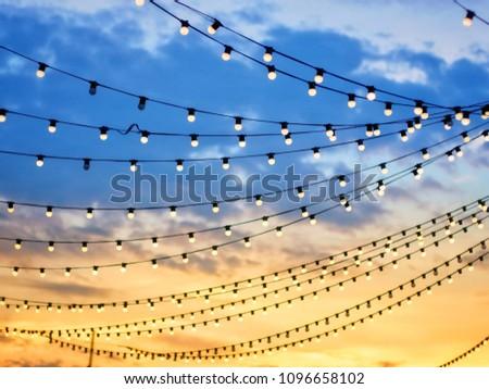 Sunset scene of light bulbs on string wire #1096658102