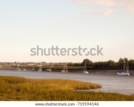 sunset scene over river through country with moored boats and clear sky; England; Essex #719594146