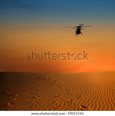 sunset scene with silhouette of a helicopter over desert