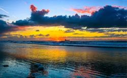Sunset sea horizon sky clouds landscape. Sunset cargo ship horizon silhouette landscape. Sunset sea cargo ship view. Sunset sea horizon landscape