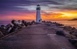 Sunset sea lighthouse rock landscape. Lighthouse sunset view. Sunset lighthouse scene. Sea sunset lighthouse landscape