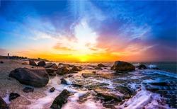 Sunset sea rocky beach landscape. Rocky sea beach sunset view. Sunset sea beach rocks landscape. Sunset sea beach scene