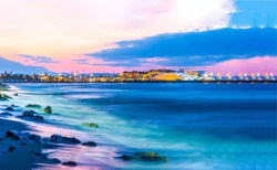 Sunset sea shore landscape. City sea shore sunset panorama. Sunset city sea shore view. Sunset sea shore panorama
