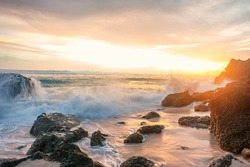 sunset seascape with rocky beach and crashing waves