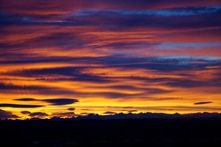 Sunset setting the sky aflame over the silhouetted Alps and the black plain of Orb
