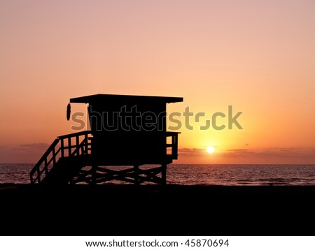 sunset shot of a baywatch lifeguard tower at malibu beach.