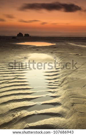 Sunset shot of the beach with sand ripples - stock photo