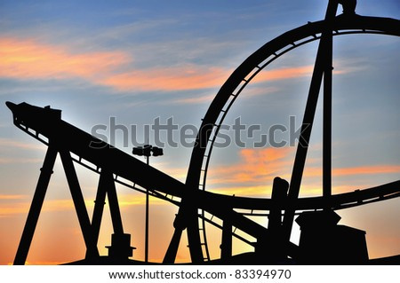 Sunset silhouette of a roller coaster in a theme amusement park