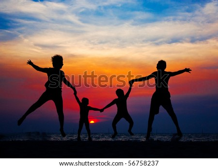 Sunset silhouette of family playing at the beach