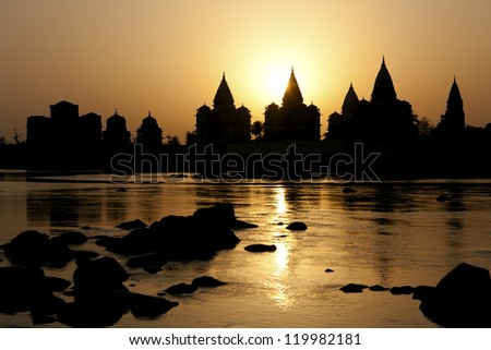Sunset silhouette of the Chhatris by the river in Orchha, Madhya Pradesh in India