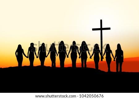 Sunset silhouette of 10 young women walking hand in hand toward a Christian Cross.