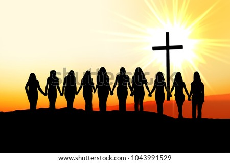 Sunset silhouette of 10 young women walking hand in hand towards the light and a Christian Cross.