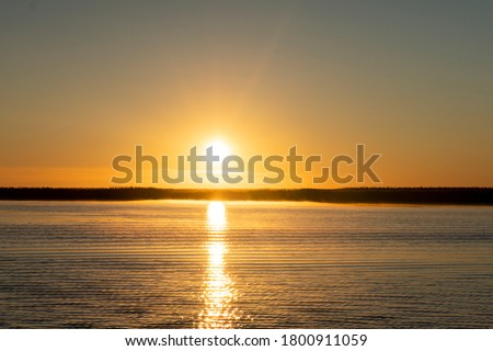 Sunset sky background. Gold sunset sky with evening sky clouds over the lake with fog.Crystal clear water texture. Small waves with water reflection