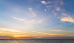 Sunset sky over sea in the evening with colorful orange sunlight cloud, Dusk sky background