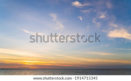 Sunset sky over sea in the evening with colorful orange sunlight cloud, Dusk sky background  Photo stock ©