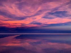 Sunset sky purple clouds shiny sea reflection. Divine sunset heaven. Magical alien landscape of planet. Space Martian nature. Mysterious lake horizon. Incredible desert view.