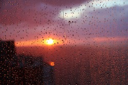 Sunset sky with clouds of the sea and house background seen through raindrops on glass